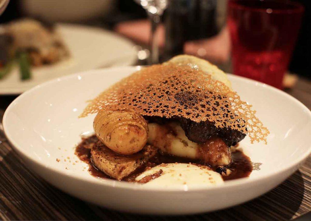Joue de boeuf confite au cacao, pommes de terre céleri rave, purée d'artichaut, huile de truffe